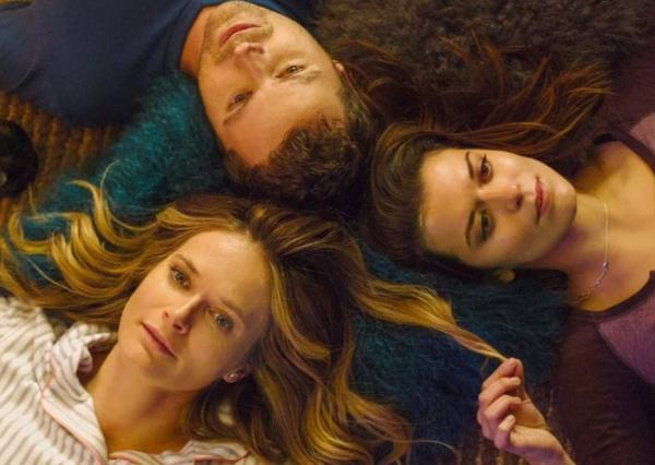 Two women and a man lying on the floor.